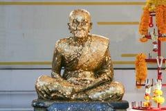 Statua dorata del monaco buddista anziano Fotografia Stock