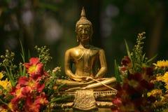 Statua dorata di Buddha che fiancheggia con i fiori immagine stock
