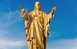 Statua dorata di Jesus Christ sopra cielo blu immagini stock libere da diritti