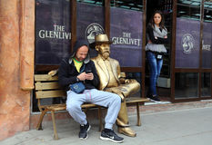 Statua dorata e due genti Fotografie Stock