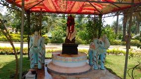 Statua indù del dio con due elefanti in tettoia e nella luce solare normale di giorno fotografia stock
