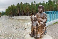 Statua mężczyzna z dzieckiem przy mostem wewnątrz w Arshan Rosja Zdjęcie Royalty Free