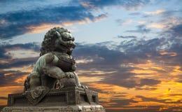 Statua maestosa del leone con la priorità bassa di incandescenza di tramonto immagine stock