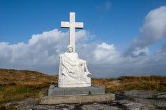 Statua maria con l'incrocio ed il cielo blu Fotografia Stock Libera da Diritti
