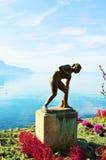 Statua minuta di Baigneuse ed alpi, il lago Lemano, Svizzera Fotografie Stock