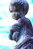 Statua pubblica del bambino da antichità contro il cielo e le nuvole fotografia stock