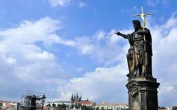 Statua sul ponticello del Charles con il castello di Praga Immagine Stock