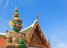 Statua verde del guardiano del demone contro il fondo del cielo blu Immagini Stock