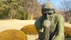 Statua verde del pensatore Auguste Rodin, mettente nudo su una roccia fotografia stock libera da diritti
