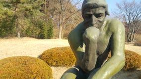 Statua verde del pensatore Auguste Rodin, mettente nudo su una roccia immagini stock libere da diritti