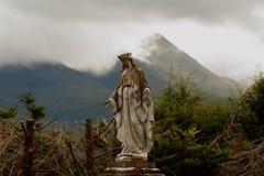 Statua z chmurnym niebem i górami Obraz Stock