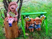 Statuarisches Sitzen des Minimädchens auf dem Stummel und der Junge und das Mädchen Stockfoto