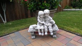 Statuary Friends. Backyard statuary of girl and boy with dog on bench Royalty Free Stock Photography
