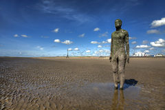 Statue. Another Place by Antony Gormley installed on Crosby Beach permanently consists of 100 statues and contributes to Liverpool European Capital of Culture 08 Royalty Free Stock Photos