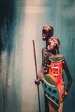 Statue africaine d'une fille avec les jeunes hommes du bleu ethnique avec le fond ocre derrière Photographie stock libre de droits