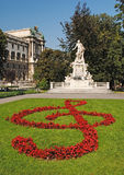 Statue of Amadeus Mozart with flower beds as treble clef in Burg Stock Images