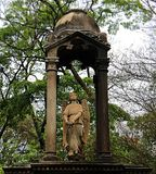 Statue of angel between columns. Small statue draws attention amidst vegetation.nCity of São Paulo / State of São Paulo / Brazil, July 05, 2019 royalty free stock photo