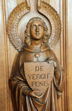 Statue of an angel at a Confessional. Statue of an angel holding a sign with the word Forgiveness in Dutch at a Confessional in the Church of Haacht, Belgium royalty free stock image
