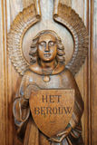 Statue of an angel at a Confessional. Statue of an angel  holding a sign with the word Repentance at a Confessional in the Church of Haacht, Belgium Royalty Free Stock Photos