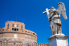 Statue of Angel with the cross and Castel Saint Angelo on the background. Rome. Italy. Stock Photos