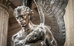 Statue of angel holding body. In building Stock Photography