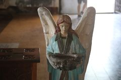 Statue of an angel inside a Church. An angel is generally a supernatural being found in various religions and mythologies. In Abrahamic religions and Stock Images