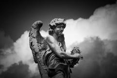 Statue of angel in Rome - B&W. Marble statue of angel on Saint Angel Bridge - Rome B&W, landscape. Dark clouds in background Stock Photo