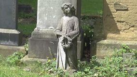 A statue of an angel. In a graveyard, UK stock footage