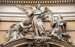 Statue of Angel about to free two slaves joined at the wrists by a real iron chain. On facade of Santissima Trinita degli Spagnoli Church in Rome, Italy Stock Images