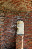 Statue of angel tucked away in brick alcove Royalty Free Stock Photography