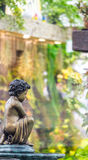 Statue of angel and waterfall in cozy garden. Royalty Free Stock Photo