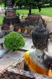 Statue antiche di Buddha che si siedono, a Wat Yai Chaimongkol al parco nazionale di Ayutthaya, la Tailandia fotografia stock