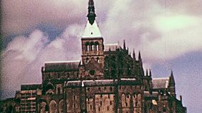 Statue of Archangel Michael. Close up of the tower with Statue of Archangel Michael atop the spire of the Historic Mont Saint-Michel castle in the 70s. Saint stock video footage
