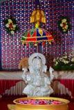 Statue argentée d'un dieu indou vinayagar et avant de la cuvette de l'eau avec des fleurs Fond blanc Photos libres de droits