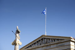 Statue of Athena and the Greek flag Stock Photos
