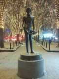 Statue auf einer schneebedeckten Straße mit feenhaften Lichtern Stockbild