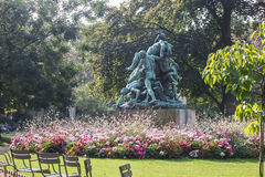 Statue of Bacchus in Luxembourg Garden, Paris. Statue of Bacchus seen from the side, with base surrounded by flower beds.Summer foliage royalty free stock photos