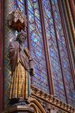 Statue and  Beautiful stained glass windows in the upper level interior Sainte-Chapelle Paris France. Statue and view of Stained Glass windows at the upper level Stock Images
