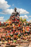 Statue of black Buddha head guarded by hundreds of roosters at Wat Thammikarat temple in Ayutthaya Province, Thailand. Also called rooster temple stock photography