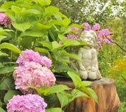 Statue blanche d'ange sur le tronçon d'arbre dans le jardin Image stock