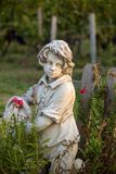 Statue of a boy holding a basket with grapes on the background of vineyards in the Saint Emilion region. France royalty free stock photo
