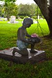 Statue of boy kneeling on grave site. Royalty Free Stock Photos