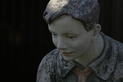 Statue of a boy pioneer. Old worn statue of a boy pioneer in shirt and tie with sad eyes Royalty Free Stock Image