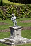Statue of a boy on a plinth in a garden Stock Photography