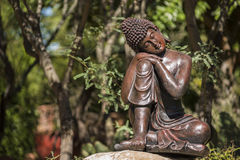 Statue of bronze buddha sleeping in a garden Stock Images