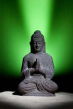 Statue of Buddha. On the sand on light green background -  Spiritual Symbol Stock Photography