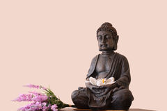 Statue of Buddha. Statue of Gautama Buddha with a candle and a flower Royalty Free Stock Images
