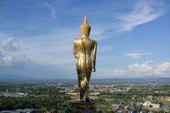 Statue of Buddha on the mountain over Nan province. Nan, Thailand - June 18, 2015: Huge golden statue of Buddha stands on mountain top to protect and watch over Royalty Free Stock Photo