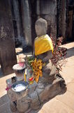 Statue of Buddha with offerings. Ancient temples of Angkor Wat, Siem Reap, Cambodia Stock Photo