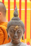 Statue of Buddha's Head. This picture shows the head of a buddhist statue, against a yellow and red background. There is part of the back of the head and robe of Stock Photography